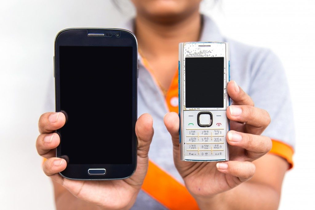 Hand holding two of mobile phone which different of technology