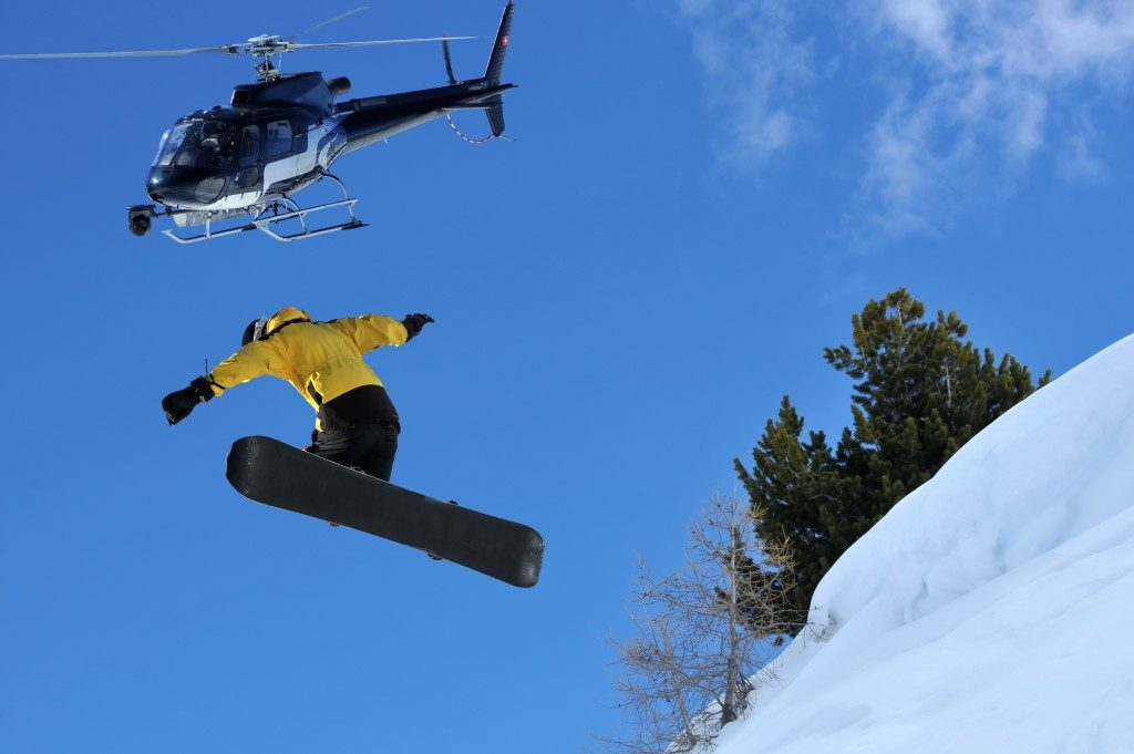 snowboarder jumping off a ridge of snow being filmed from a helicopter