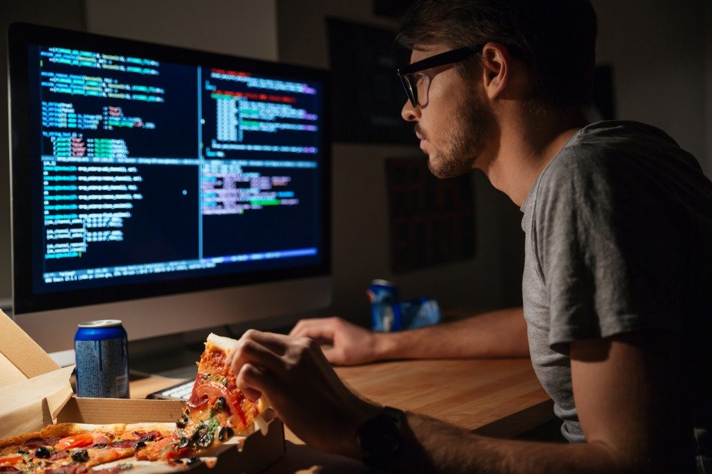 man coding while eating pizza