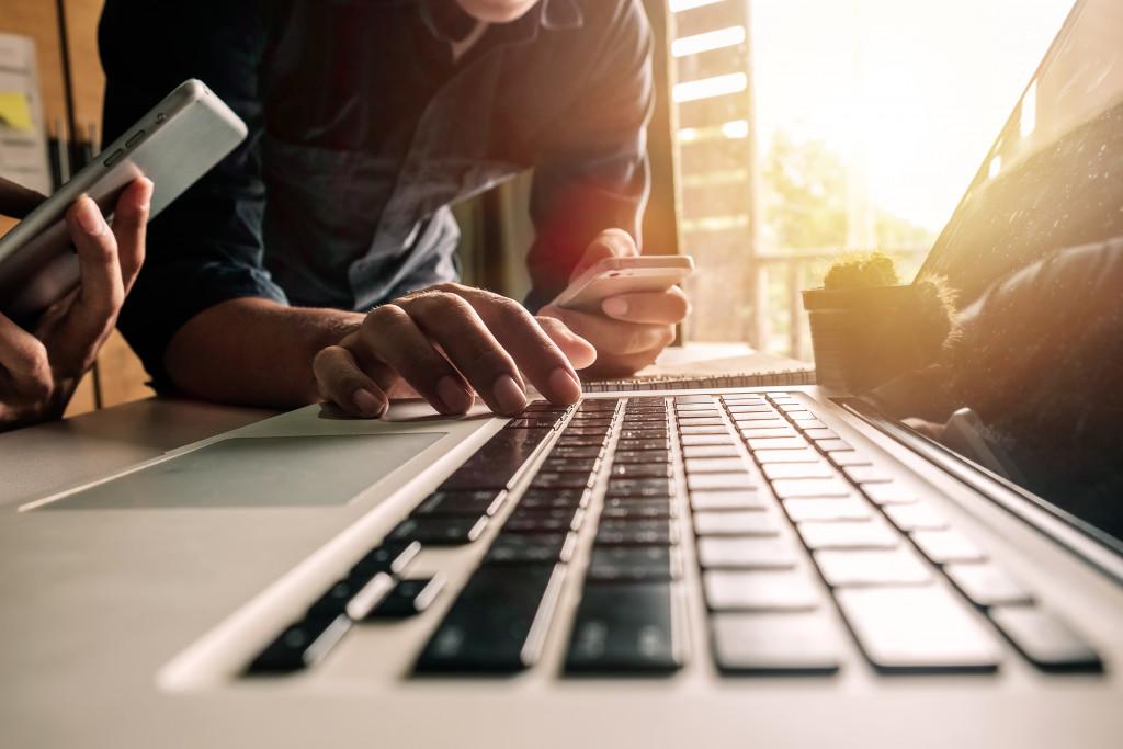 men typing on laptop holding cellphones